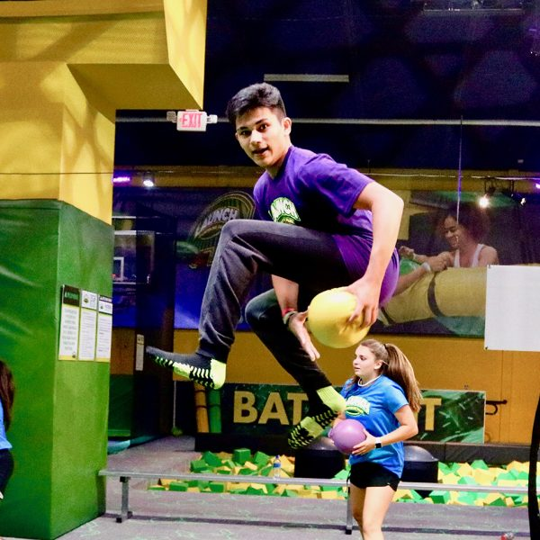 Boy jumping in the air playing dodgeball at Launch