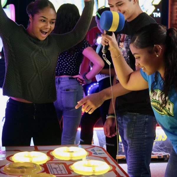 Teens playing arcade games at indoor trampoline park