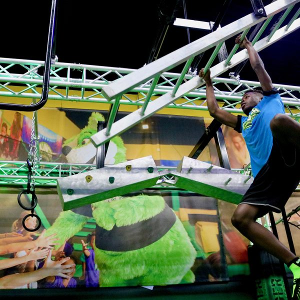 Boy climbing on monkey bars in The Challenger Ninja Course at Launch Trampoline Park