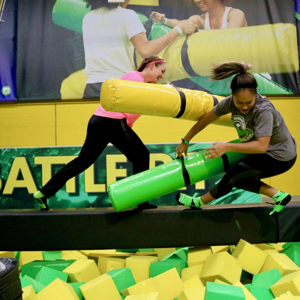 Teen girls battling with foam jousts on a balance beam at Launch Trampoline Park