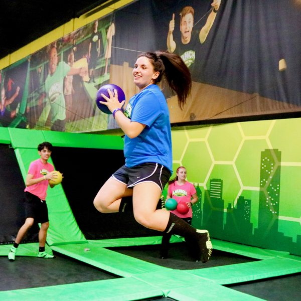 Girl jumping in the air playing dodgeball at Launch Trampoline Park