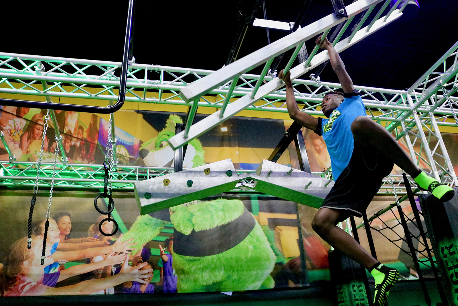 57882e00fb Boy climbing on monkey bars in The Challenger Ninja Course at Launch Trampoline  Park